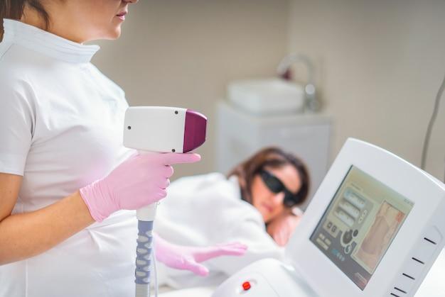 Kobieta w profesjonalnej klinice kosmetycznej podczas depilacji laserowej. zabieg depilacji. gładka skóra