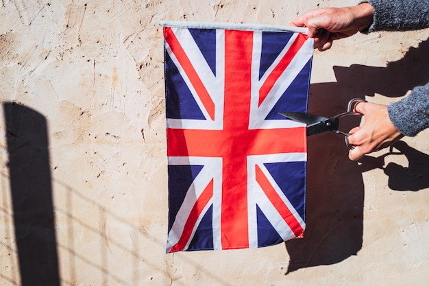 Kobieta w proteście przecina nożyczkami brytyjską flagę.