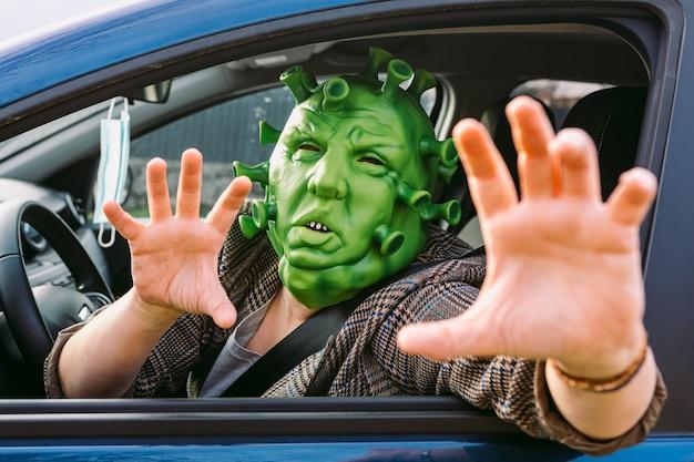 Kobieta w przebraniu - maska koronawirusa covid-19 prowadząca samochód, wyglądająca przez okno, strasząca