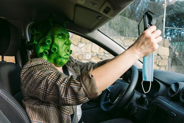Kobieta w przebraniu - maska koronawirusa covid-19 w samochodzie zawieszająca maskę ochronną w lusterku obrysowym