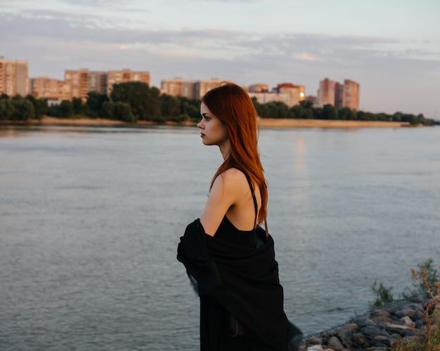 Kobieta w przezroczystej czarnej tkaninie pozuje w modzie natury tak elegancki styl