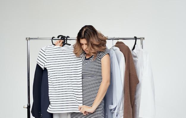 Kobieta w przymierzalni z ubrania w ręku koszuli na zakupy.
