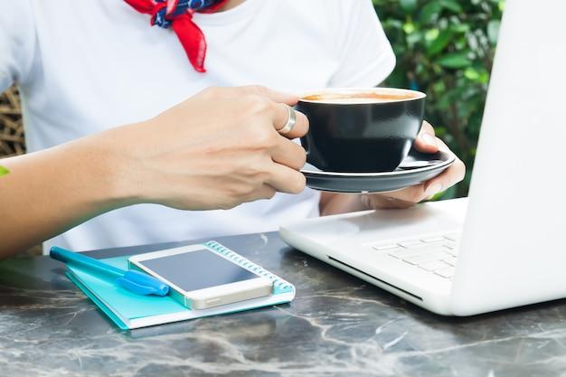 Kobieta w przypadkowej stylowej białej koszulce pije kawę