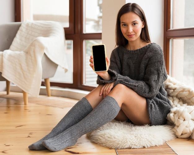 Kobieta w przytulnych ubraniach siedzi na dywanie z pustym telefonem