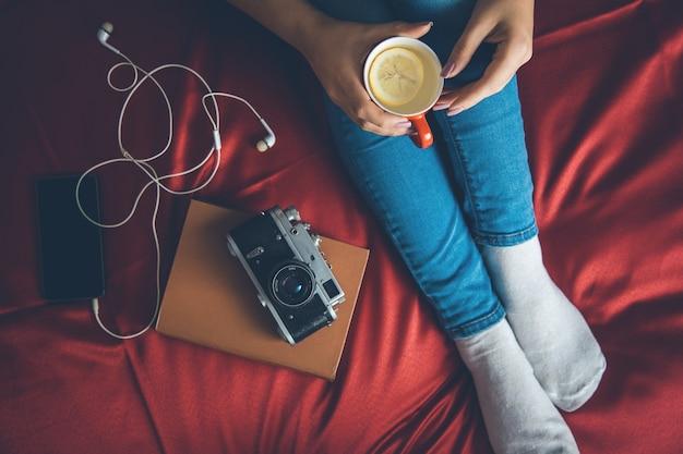 Kobieta w przytulnym swetrze na łóżku ze starą książką i filiżanką herbaty z mlekiem w rękach, widok z góry