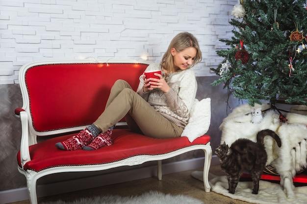 Kobieta w przytulnym swetrze siedzi w pobliżu choinki na czerwonej kanapie i trzyma gorący kubek. kot pozostaje w pobliżu choinki