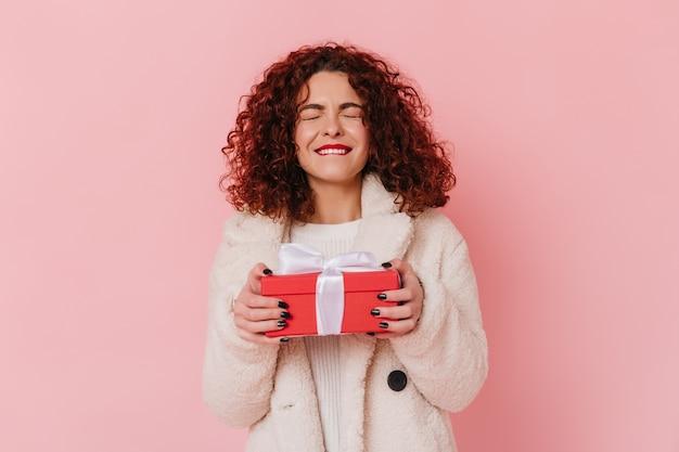 Kobieta w radosnym oczekiwaniu trzyma prezent. pani z ciemnymi kręconymi włosami na różowej przestrzeni.