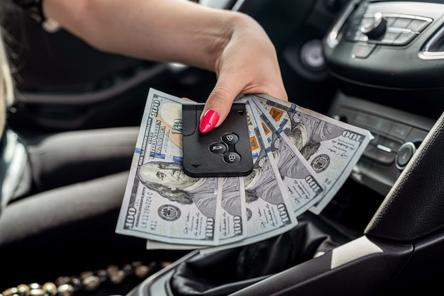 Kobieta w ręce nadajnika dolarów w samochodzie w środku, koncepcja korupcji i łapówek