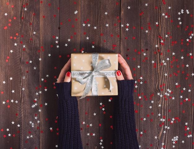 Kobieta w ręce trzyma pudełko świąteczne