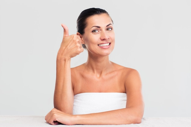 Kobieta w ręcznik pokazuje kciuk do góry