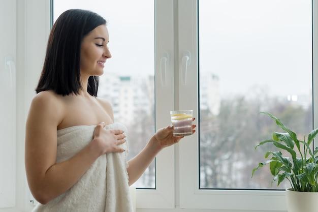 Kobieta w ręcznik ze szklanką wody z cytryną