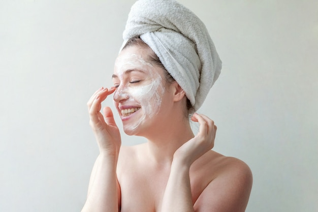 Kobieta w ręczniku na głowie z białą odżywczą maską lub creme na twarzy