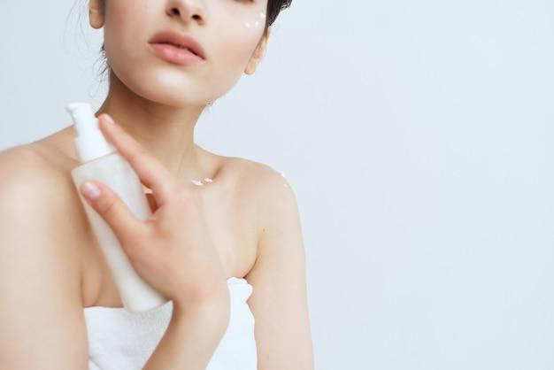 Kobieta w ręczniku nakłada krem, aby oczyścić zdrowie ciała