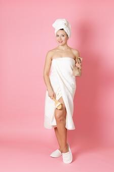 Kobieta w ręczniku trzyma peeling i masuje nogę drewnianą szczotką