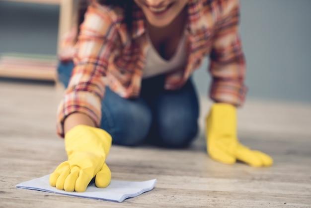 Kobieta w rękawice ochronne, uśmiechając się podczas czyszczenia podłogi. koncepcja czyszczenia