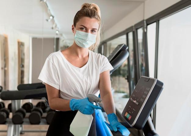 Kobieta w rękawiczkach do czyszczenia sprzętu na siłowni podczas pandemii