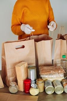 Kobieta w rękawiczkach medycznych pakująca żywność do darowizny