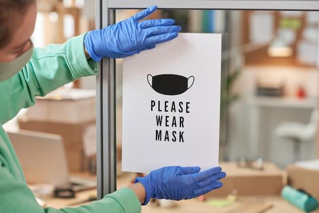 Kobieta w rękawiczkach ochronnych, naklejanie reklamy na szklanej ścianie w biurze