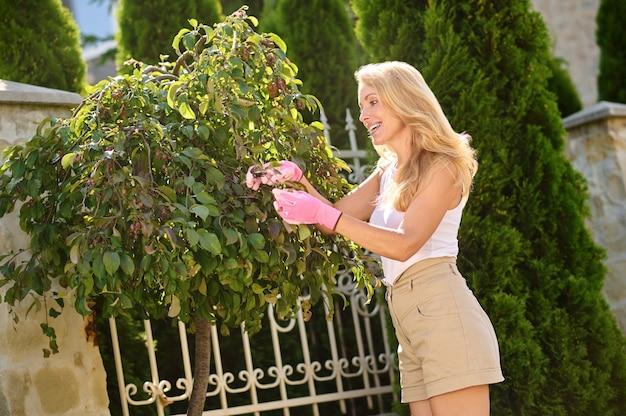 Kobieta w rękawiczkach ochronnych robi ogrodnictwo