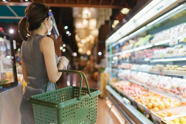 Kobieta w rękawiczkach, osłona twarzy i maska wybierając warzywa. panika na zakupach podczas pandemii wirusa korony.