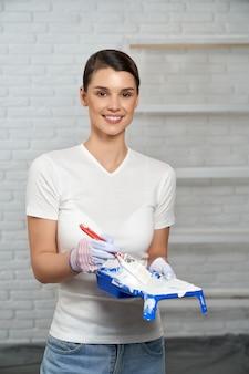 Kobieta w rękawiczkach trzymająca pędzel i tacę z farbą