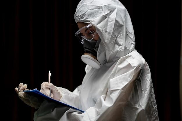 Kobieta w rękawiczkach z biohazard chemiczny strój ochronny i maskę. pisze raport na papierze.