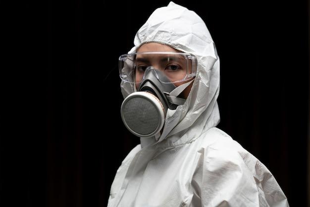 Kobieta w rękawiczkach z biohazard chemiczny strój ochronny i maskę.