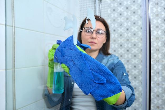 Kobieta w rękawiczkach z szmatką i detergentem, do mycia i polerowania szkła pod prysznic