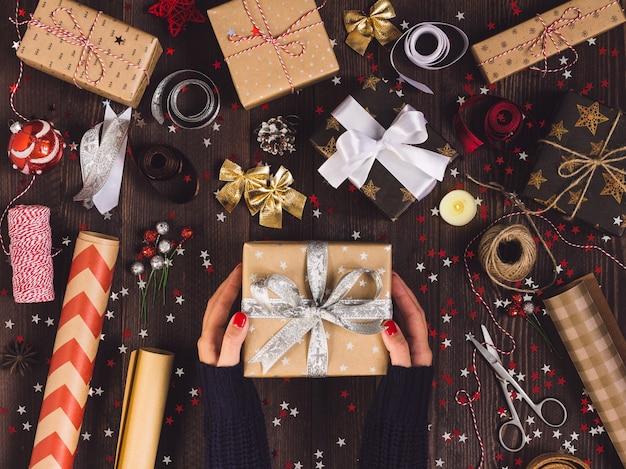 Kobieta w ręku trzyma nowy rok prezenta pudełko