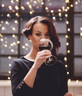 Kobieta w restauracji trzyma kieliszek do wina