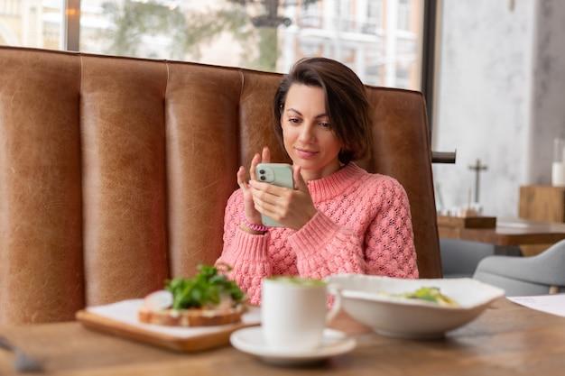 Kobieta w restauracji w ciepłym swetrze patrzy na telefon, pyszne zdrowe śniadanie i matcha latte na stole