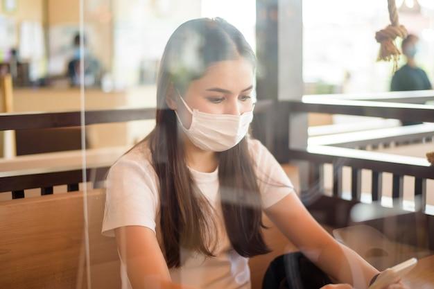 Kobieta w restauracji z protokołem dystansowania społecznego i maską na twarzy
