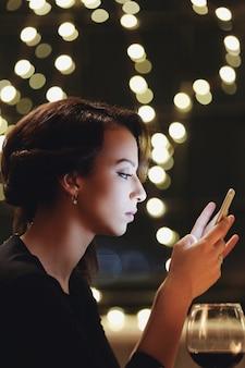 Kobieta w restauracji za pomocą smartfona