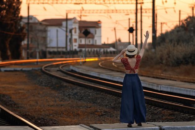 Kobieta w retro kapeluszu macha na pożegnanie z pociągiem.