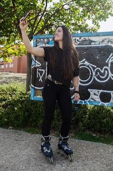 Kobieta w rolkowych łyżwach bierze selfie