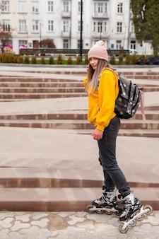 Kobieta w rolkowych ostrzach pozuje w mieście
