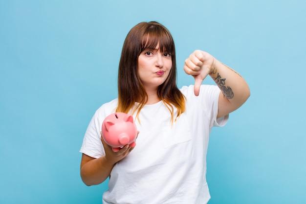 Kobieta w rozmiarze plus czuje się zła, zła, zirytowana, rozczarowana lub niezadowolona, pokazując kciuki w dół z poważnym spojrzeniem
