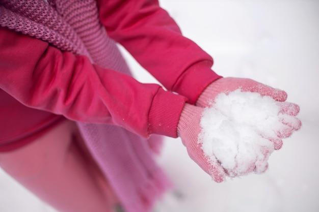 Kobieta w różowe ubrania rękawiczki spodnie kurtka trzyma śnieg w dłoniach