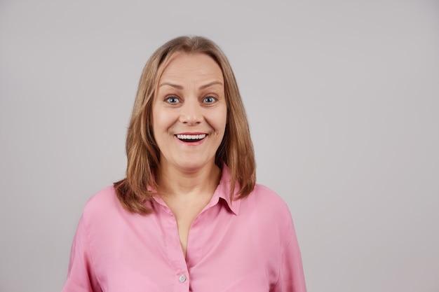 Kobieta w różowej bluzce uśmiechając się, patrząc w kamerę