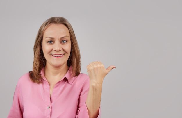 Kobieta w różowej bluzce uśmiechnięty patrzy w kamerę
