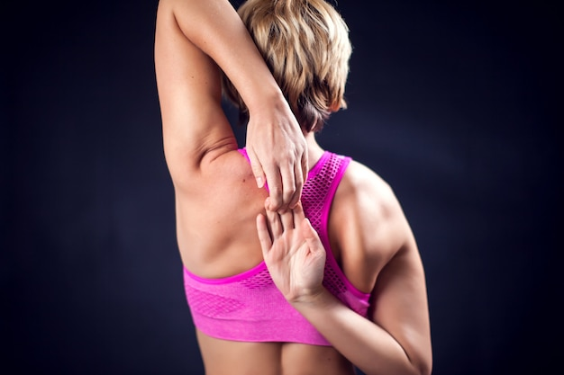 Kobieta w różowej górze rozciąga triceps przed czarnym tłem. koncepcja fitness, stylu życia i zdrowia