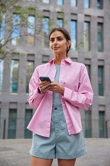 Kobieta w różowej koszulce i szortach przegląda telefon komórkowy pobiera aplikację do wyszukiwania trasy czyta czat zadowolony z dobrego internetu spaceruje po ulicy w budynku centrum biznesowego