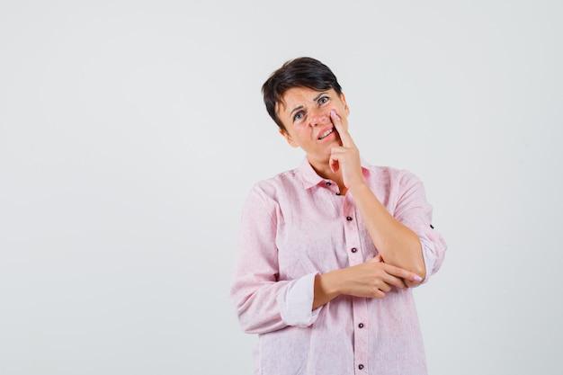 Kobieta w różowej koszuli odwracając wzrok i niepewny, widok z przodu.