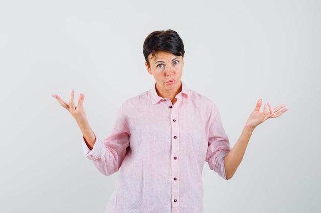 Kobieta w różowej koszuli podnosząc ręce w geście przesłuchania i patrząc zdziwiona, widok z przodu.