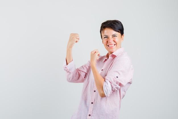 Kobieta w różowej koszuli pokazując gest zwycięzcy i patrząc błogi, widok z przodu.