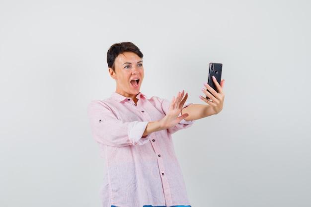 Kobieta w różowej koszuli rozmawia na czacie wideo i wygląda podekscytowany, widok z przodu.
