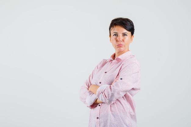 Kobieta w różowej koszuli stoi ze skrzyżowanymi rękami i wygląda pewnie, widok z przodu.