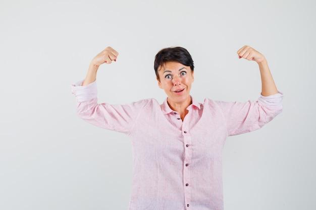 Kobieta w różowej koszuli ukazująca mięśnie ramion i wyglądająca potężnie, z przodu.