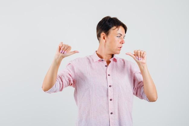 Kobieta w różowej koszuli, wskazując na siebie kciukami i patrząc skupiony, przedni widok.