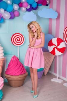 Kobieta w różowej sukience na tle ozdobione ogromnymi cukierkami i lodami